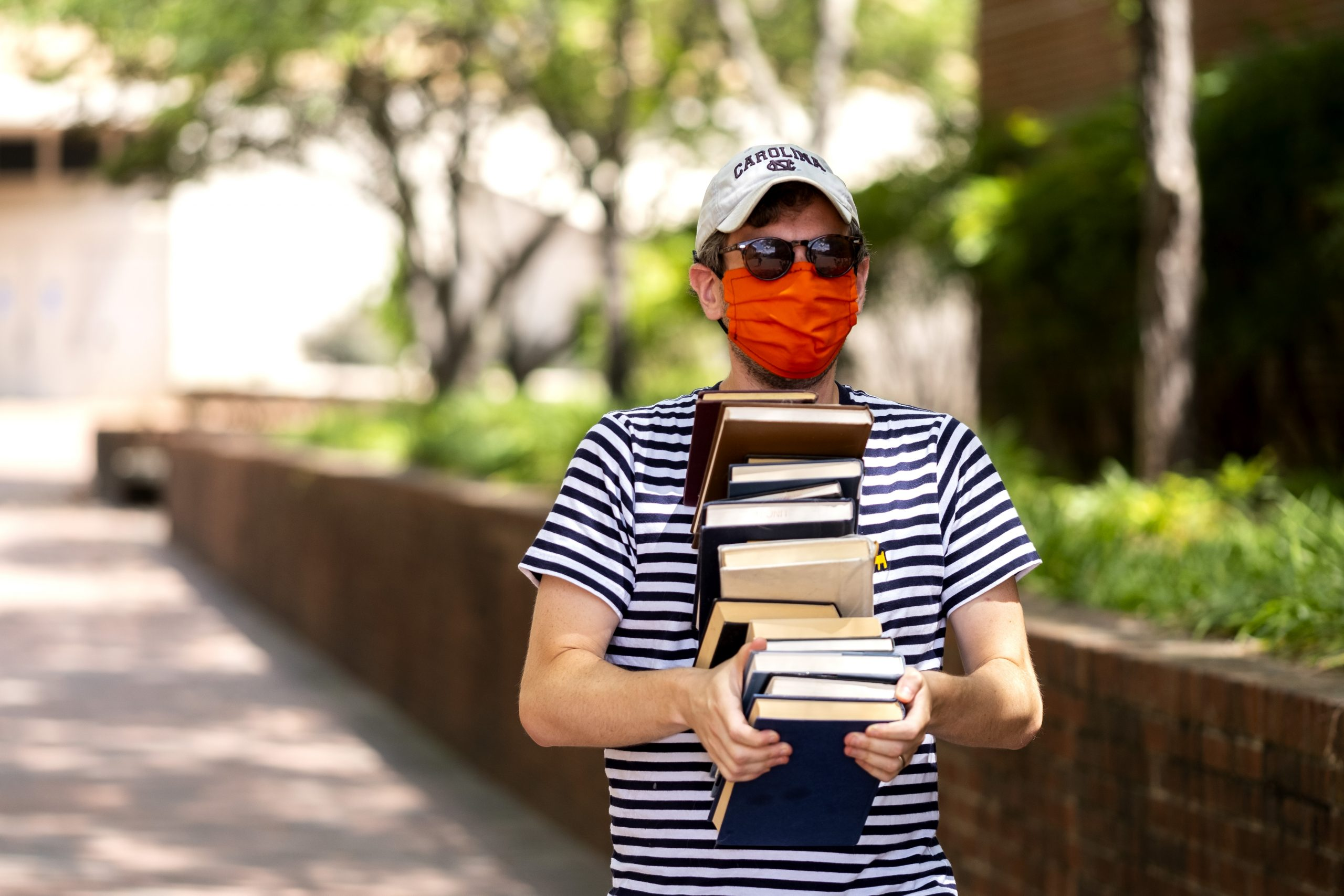 Man in mask carrying books