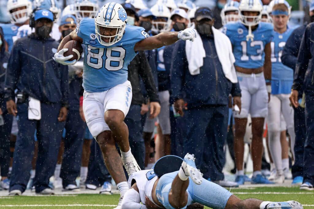 Carolina football player running with ball on field.